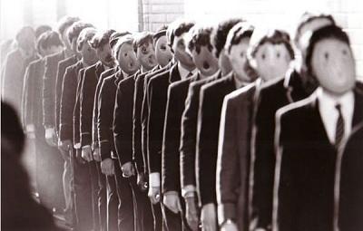 Scena da The Wall dei Pink Floyd, bambini in fila con indosso maschere