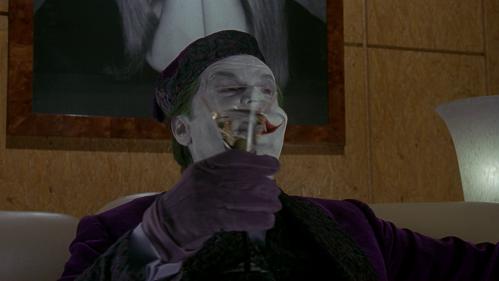 Joker che ridacchia tenendo un drink in mano. Da Batman 1989