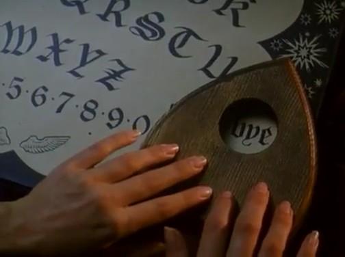 Tavola ouija con planchette che indica la parola bye