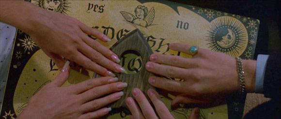 Scena dal film Witchboard Spiritika, mani sulla tavola ouija
