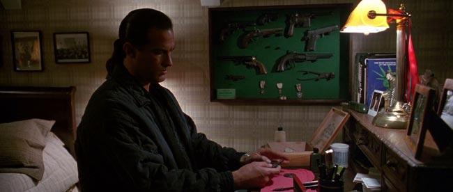 Steven Seagal che pulisce una pistola da pugno storica, scena dal film Programmato per uccidere